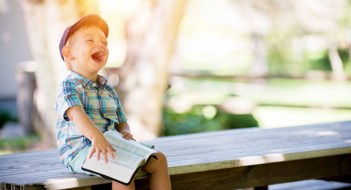 Kid laughing holding the Bible